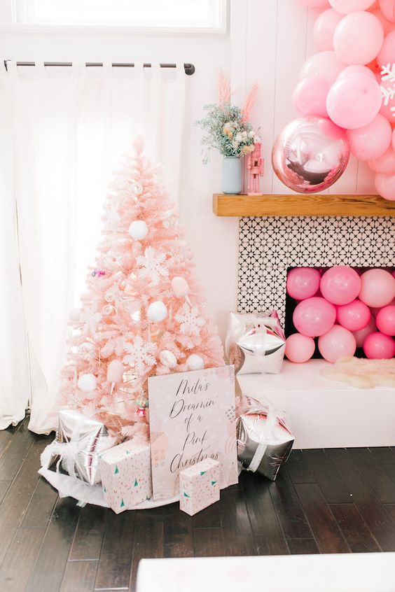 a blush Christmas tree with white ornaments, printed gift boxes, pink balloons in the fireplace and over it