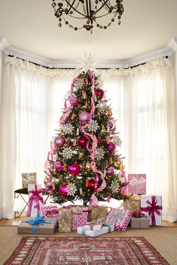 a bold Christmas tree decorated with pink and pink sequin ornaments, pink ribbons, lights and large snowflakes and a large star on top