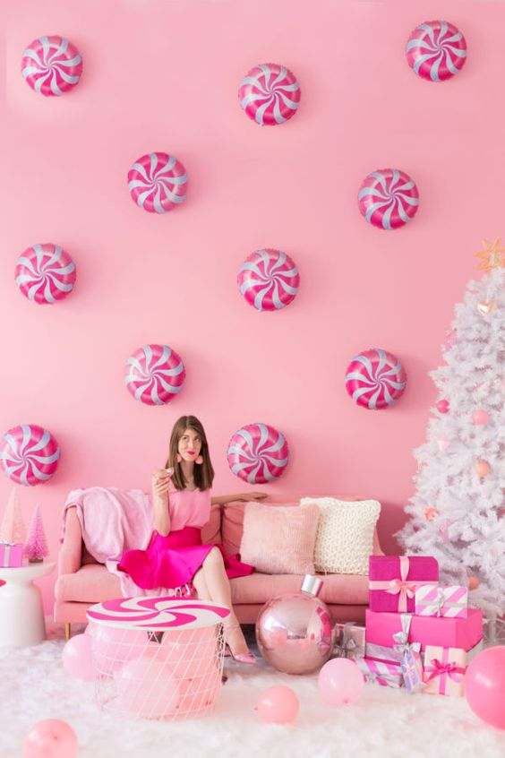 a pink holiday space with peppermints on the wall, pink furniture and balloon and pink ornaments on a white Christmas tree