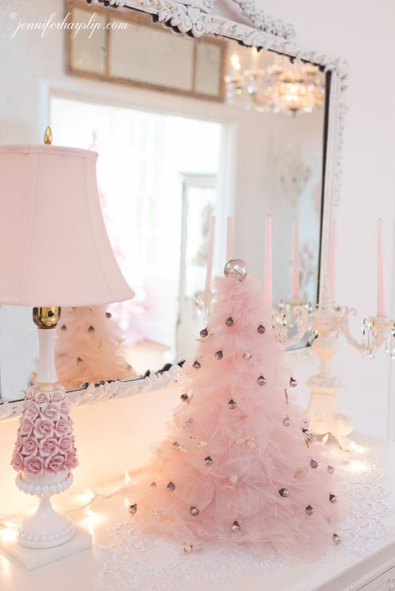 a pink ruffle Christmas tree decorated with tiny metallic ornaments adds a cool and chic glam feel to this vintage space