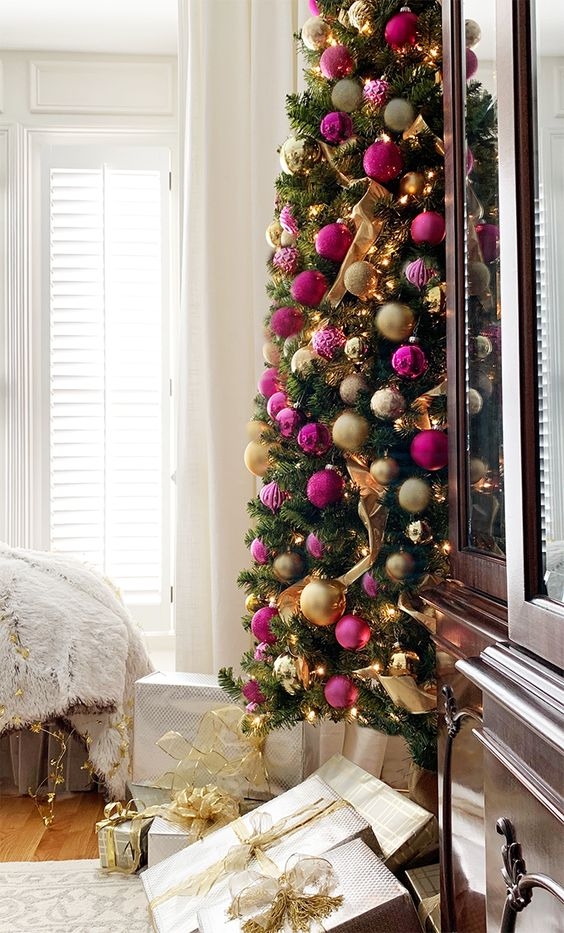 a refined Christmas tree with lights, gold and hot pink and fuchsia ornaments and ribbons is a gorgeous idea for a chic holiday space