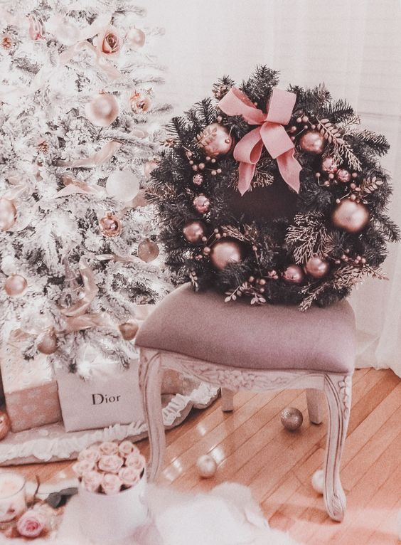 a refined and glam fir Christmas wreath dotted with pink ornaments and a large bow is a chic idea to bring a touch of glam