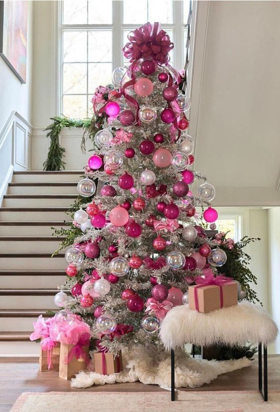 a silver Christmas tree decorated with pink, fuchsia, sheer and silver ornaments and a large fuchsia bow on top