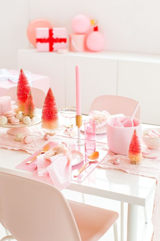 a simple and modern pink Christmas tablescape with light pink linens, candles, acrylic chargers, ornaments and ombre tinsel trees