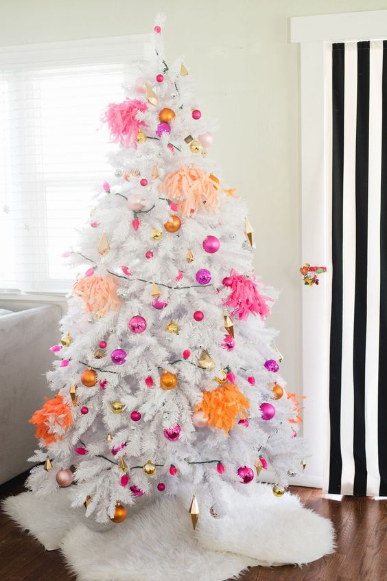 a white Christmas tree with hot pink, fuchsia, gold and orange ornaments and bright tassels is all about modern decor and bright colors