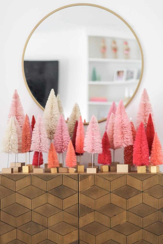 an arrangement of coral and pink and red tinsel Christmas trees on your console table will give a modern festive feel to the entryway