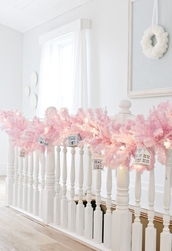 beautiful holiday railing decor with a pink fir branch garland, lights and mini houses hanging on it is a lovely idea
