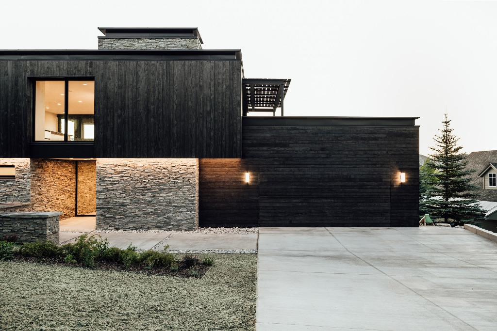 02 The exterior of the house is done with blackened wood and stone to connect it to the surroundings