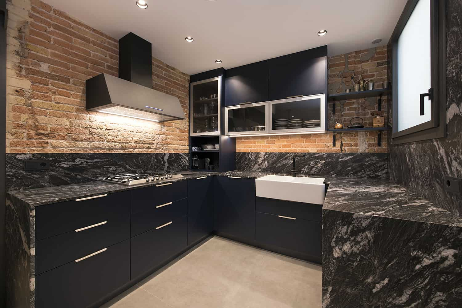 The kitchen is all industrial, with black cabinetry, black marble countertops and backsplashes, red brick walls