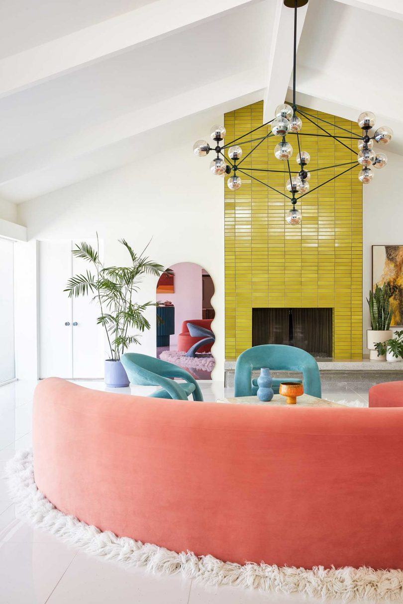 The living room shows off a lemon yellow tile fireplace, some bright furniture, a mid-century modern chandelier and potted plants