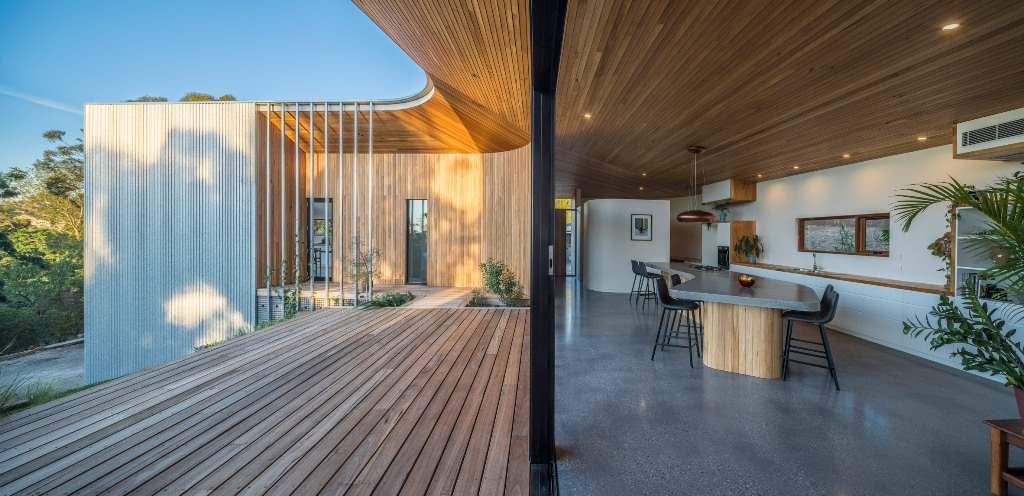 There's a long deck dotted with growing greenery and plants and the glazed facade allows the views and light