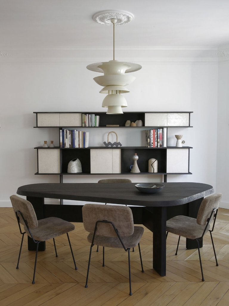 The dining space shows off a dark wooden table, some cool chairs and a refined storage piece at the wall