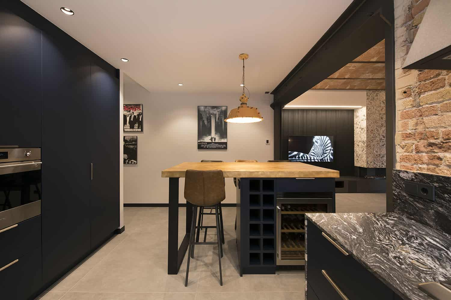 The kitchen island features wine storage, light stained butcherblock countertop and tall leather stools