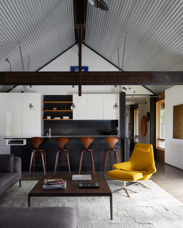 The open layout features a kitchen, a dining space and a living room, with sleek white cabinets, a grey sectional and a yellow lounger