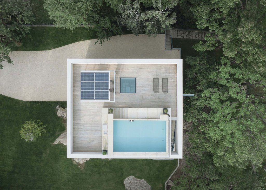 The roof features a terrace with a pool, some loungers, photovoltaic panels and a cool view