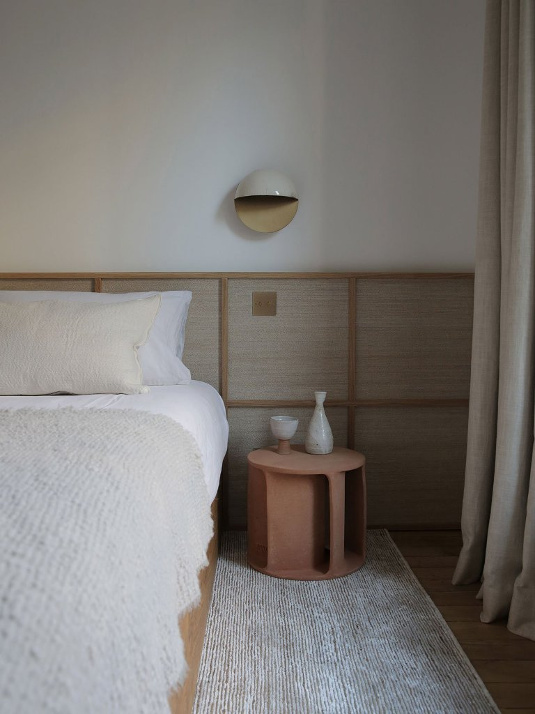 The bedroom is very relaxing and calm, with wooden panels, terracotta nightstands, wall sconces