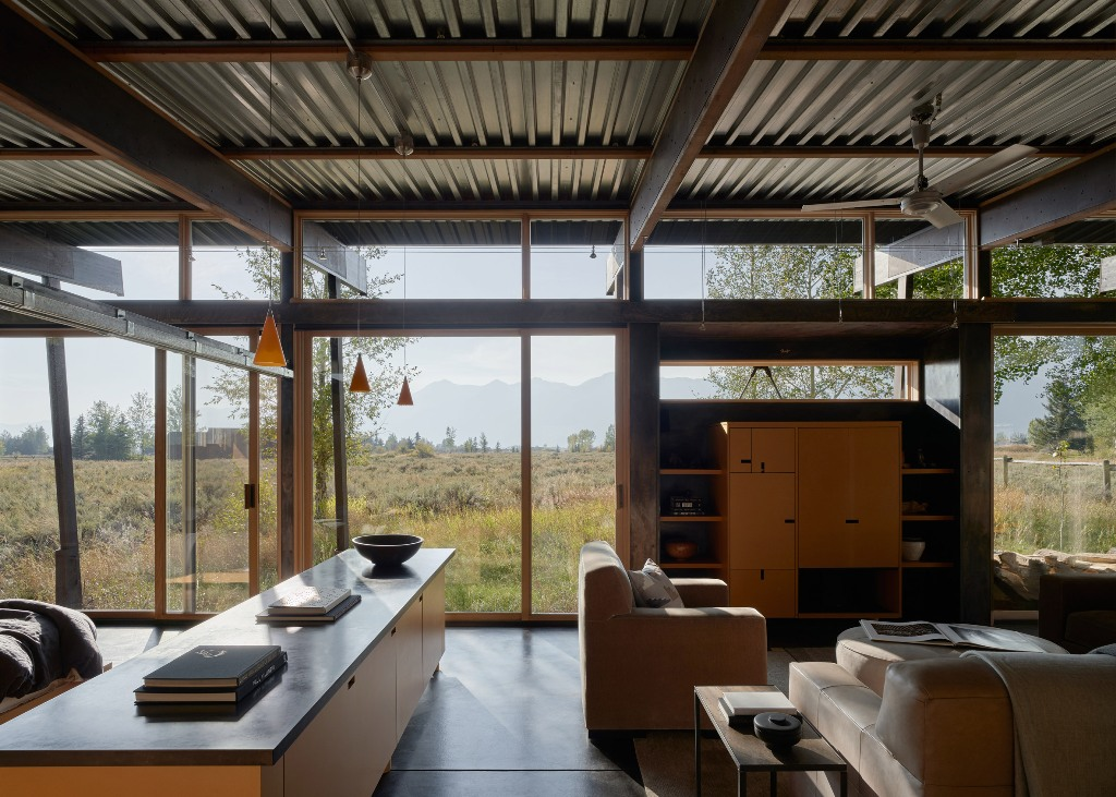 Most of the walls are glazed for light and views, and the furniture is contemporary and mid-century modern