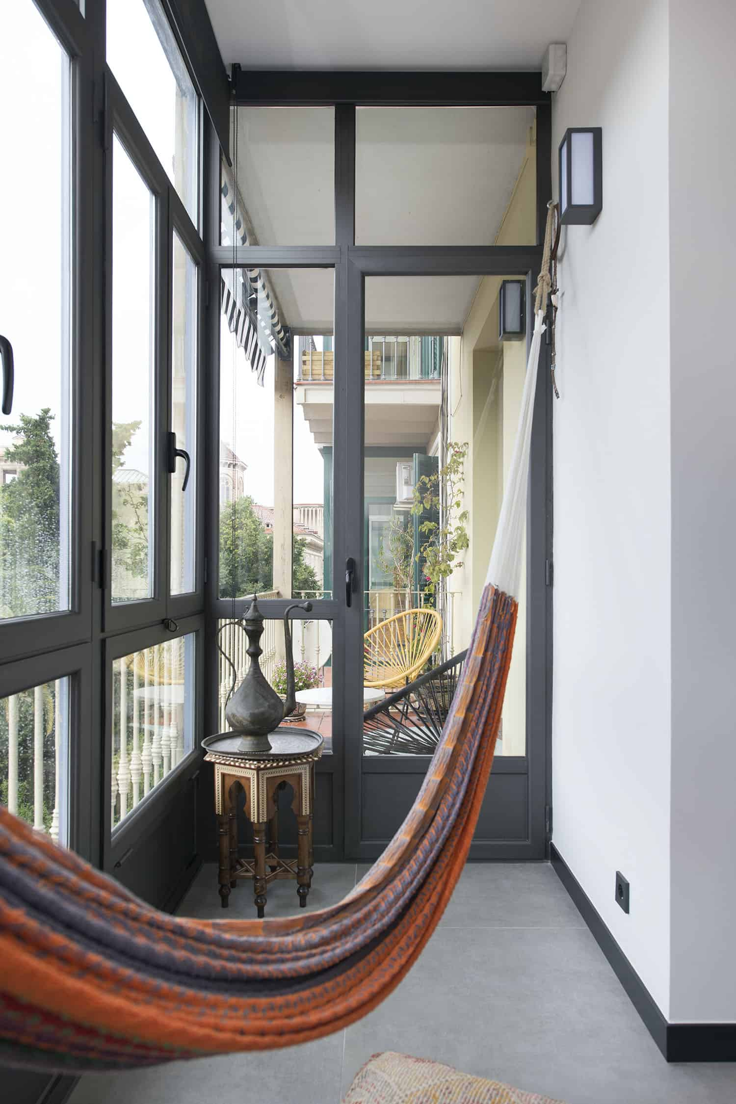 The balcony is glazed and is decorated in boho style, with a boho hammock, a boho table, a tray and a teapot