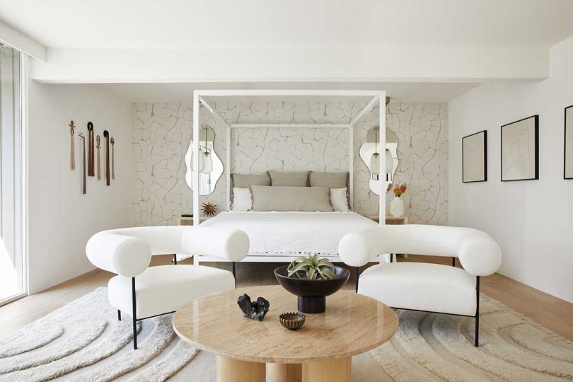 The bedroom is neutral, with a wallpaper wall, white furniture, a wooden table and a gallery wall