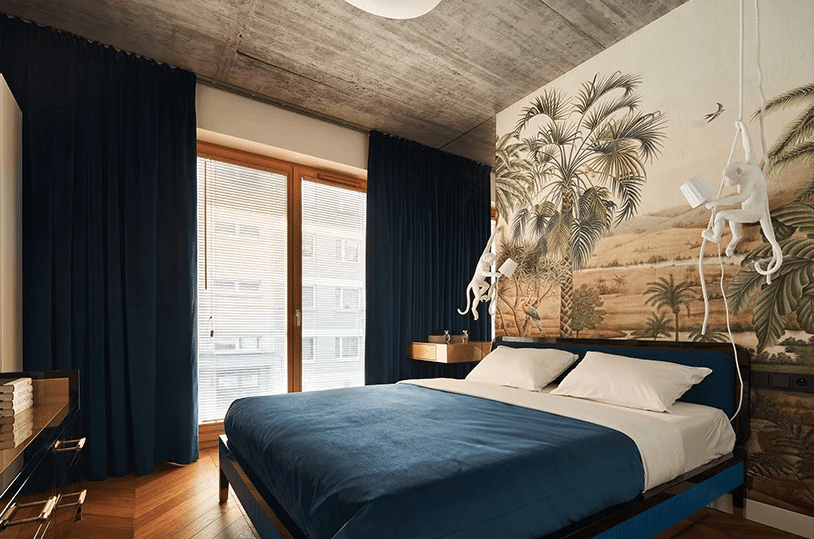 The bedroom shows off a tropical print wall, floating nightstnads, hanging monkey pendants, a navy bed and navy velvet curtains