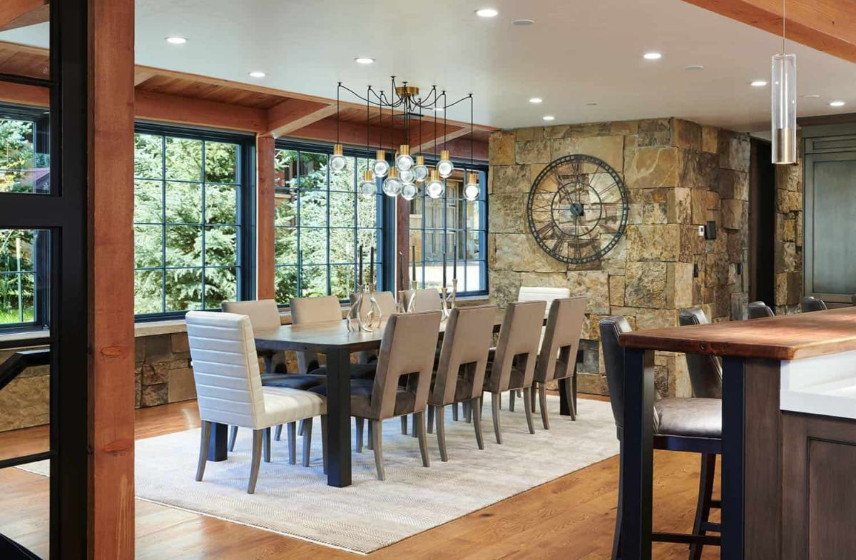 The dining area is framed by a wall of farmhouse windows with a lovely view of the garden