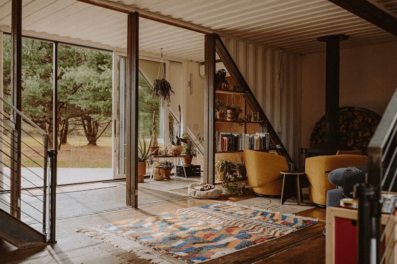 The foyer runs into a living area, which is done with boho rugs and bright furniture, with a hearth and a triangle shelf