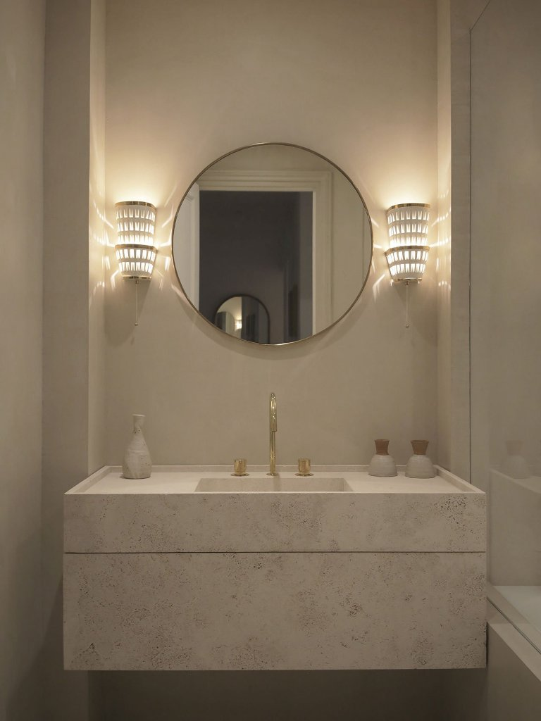 The bathroom is neutral, with a marble vanity, gold fixtures and chic wall sconces