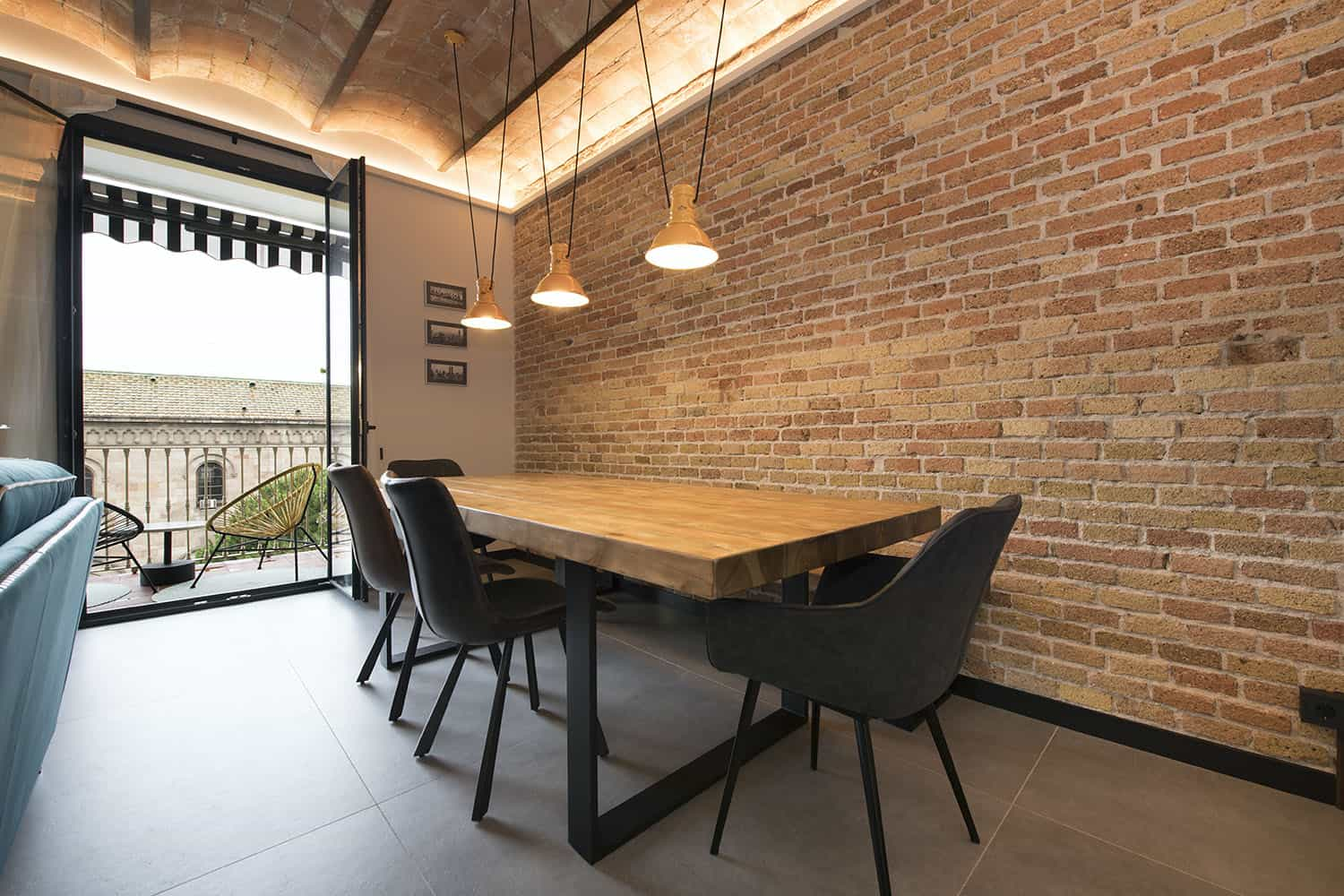 The dining space is industrial, with a brick wall, a wooden table and black chairs plus pendant lamps