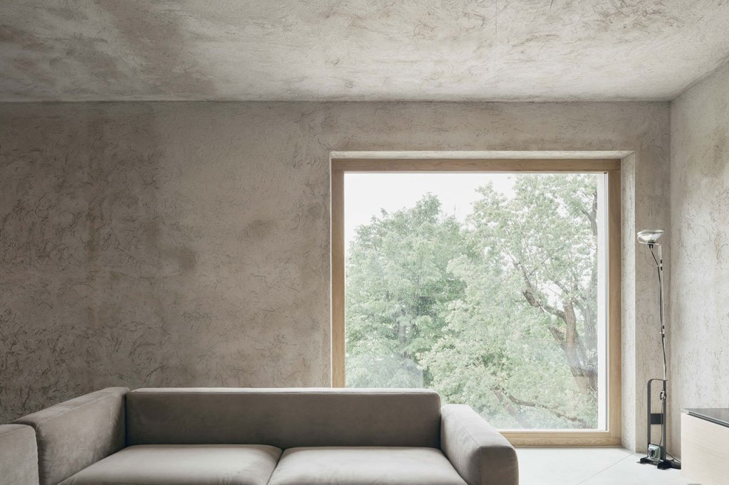 The living room features nothing but minimalist furniture and lamps and amazing views