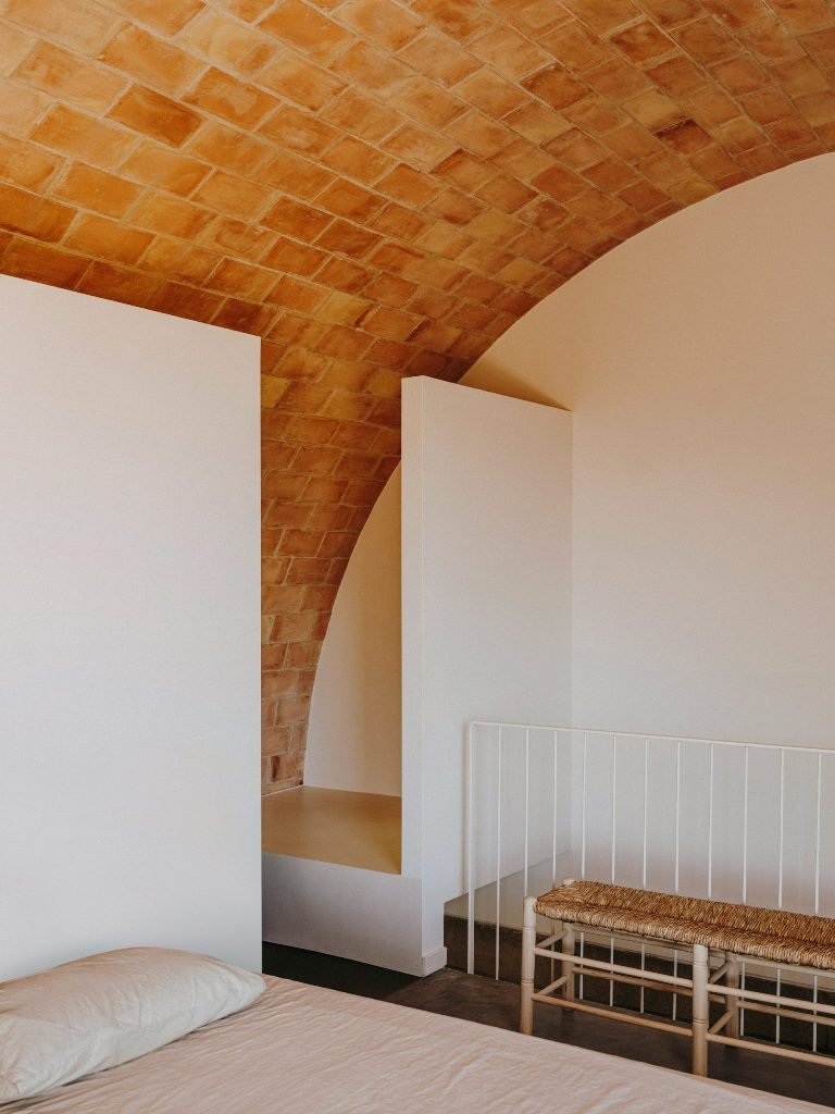 The main bedroom sits beneath an arched first floor and a very cool woven bench