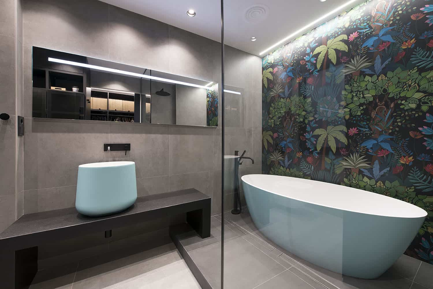 The bathroom is clad with grey tiles, a dark floral wall makes a statement and aqua appliances add to the space