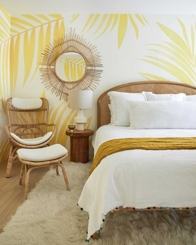 This sunny yellow bedroom shows off leaf printed wallpaper and a rattan mirror and chair