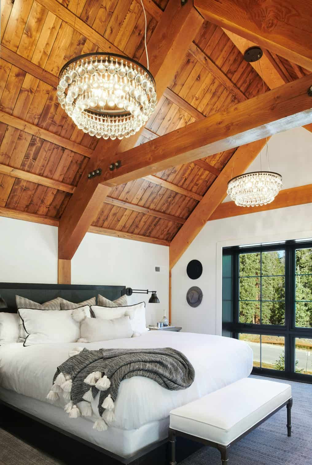 The bedroom features a slanted ceiling accent with crystal chandeliers and cool views