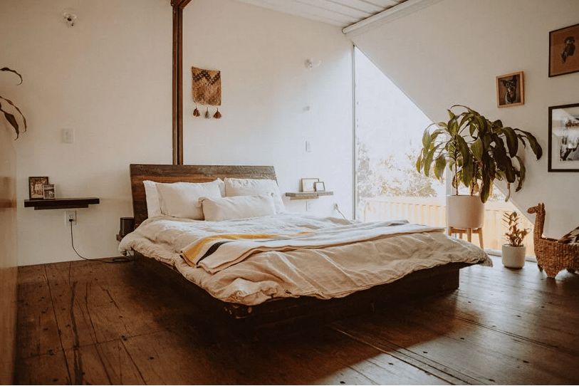The bedroom is done with a triangle window, potted plants, a gallery wall and a stained bed with boho bedding