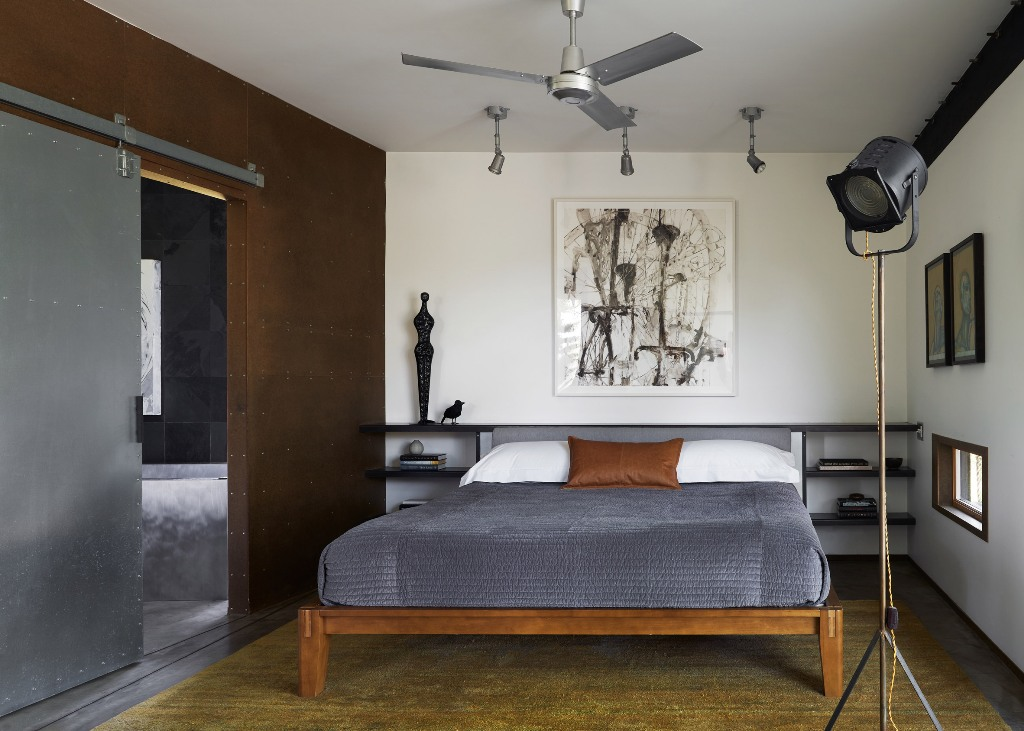 The bedroom is very laconic, with a bed, some open shelves, an artwork and lamps