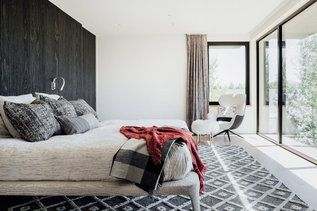 The bedroom shows off a timber accent wall, grey and white furniture and decor and an access to the terrace