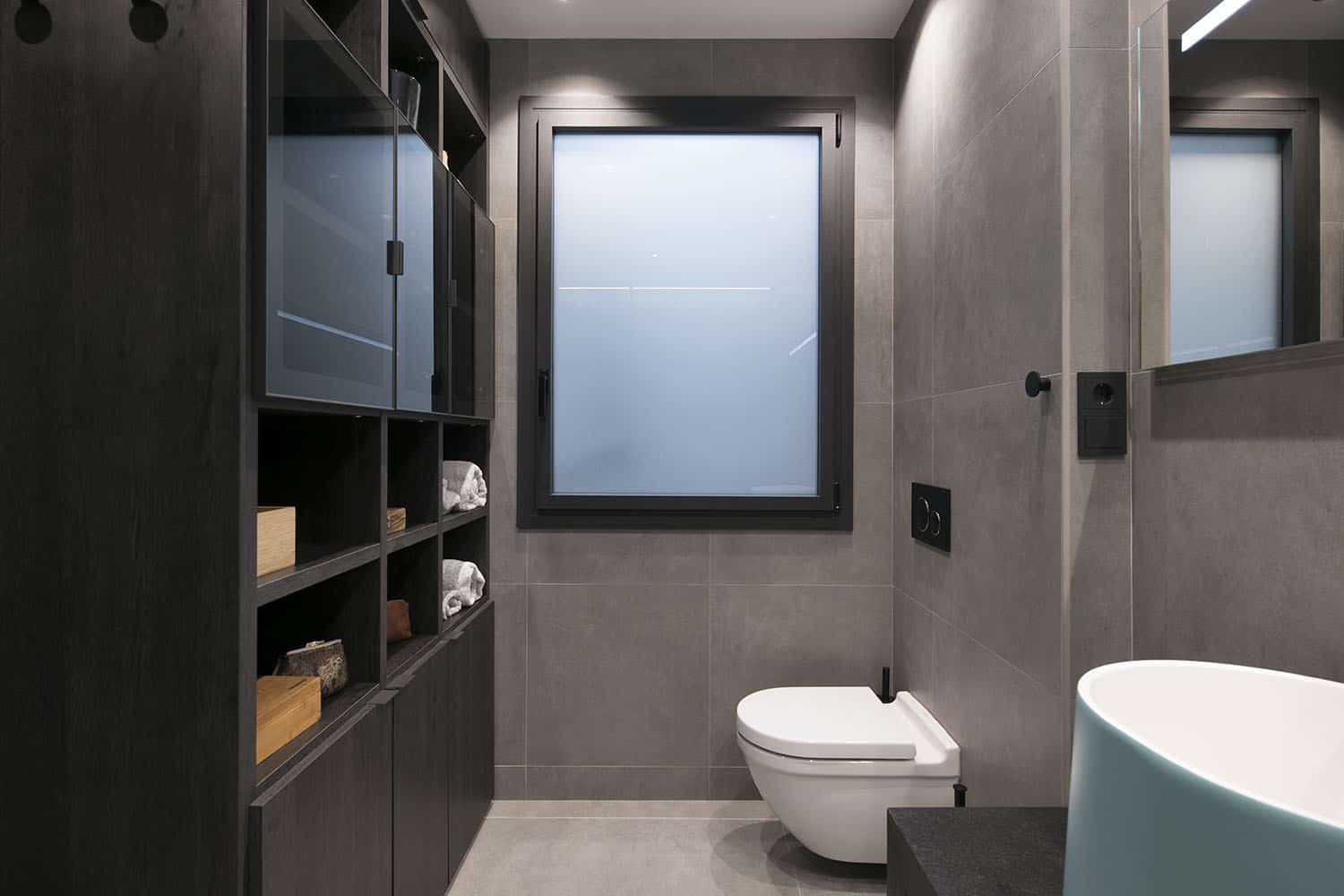 There's dark furniture that contrasts the light tiles and appliances