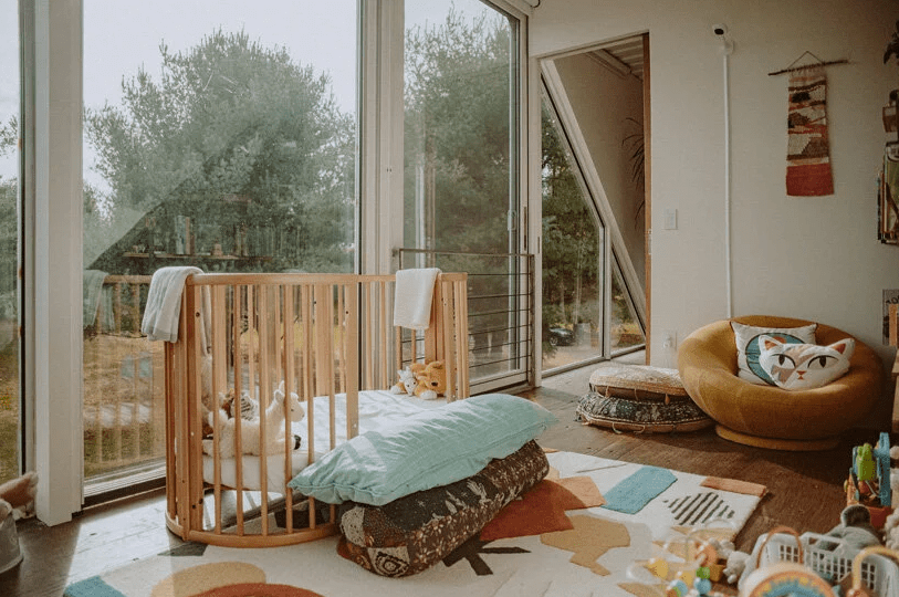 The nursery is done with a glazed wall, some pretty boho furniture and poufs, a crib and colorful toys and rugs