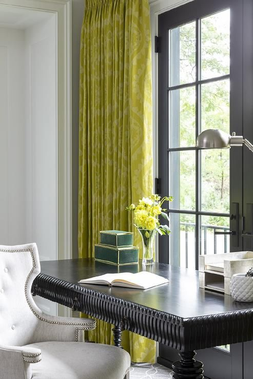 a black spindle desk paired with a light gray velvet chair and yellow damask curtains for a very chic and exquisite home office