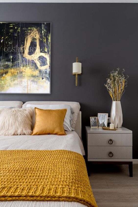 a bold bedroom with a graphite grey wall, creamy furniture, creamy and yellow bedding, a bold artwork over the bed