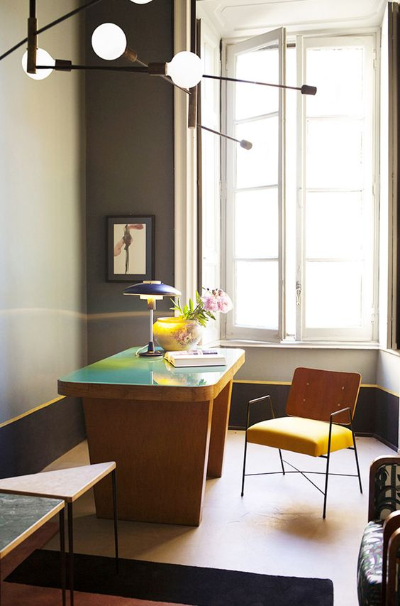 a bold home office with a grey walls, yellow edges, a catchy yellow desk with a green countertop, a yellow chair, a table lamp and some pendant ones
