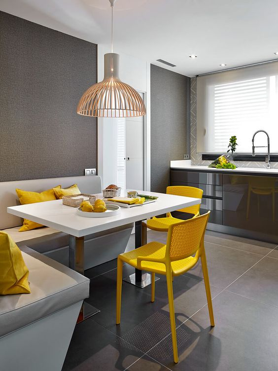 a bold modern dining nook in the kitchen, with a corner seat, a table, bright yellow chairs and a pretty lamp