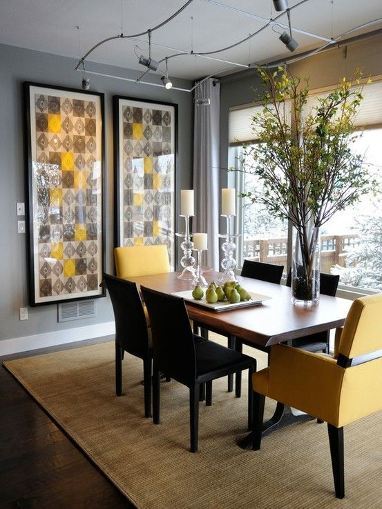 a bold modern dining room with grey walls, a panoramic view, bold artworks, a dining table, black and yellow chairs and catchy lights