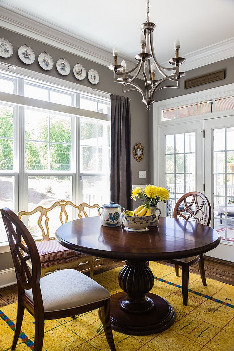 a bold vintage dining room with grey walls, a large window, a heavy round table and chairs, decorative plates and a bold yellow rug