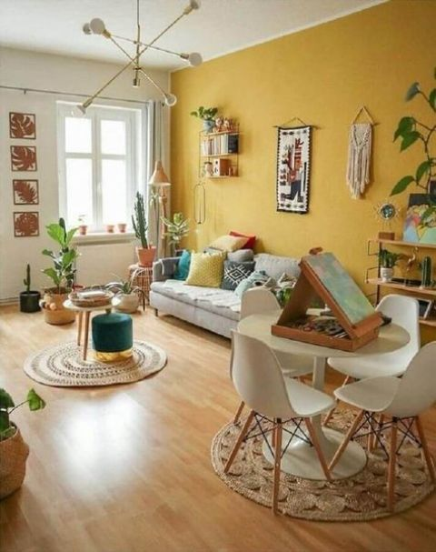 a bright boho living room with a yellow accent wall, neutral furniture, books, potted plants, touches of greenery and a jute rug