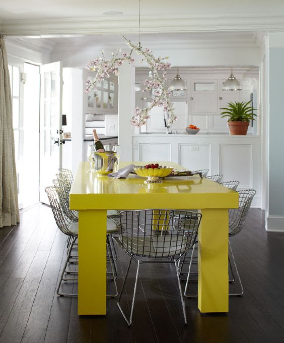 a bright contemporary dining space with a neon yellow table and grey metal chairs plus a whimsical cherry blossom chandelier