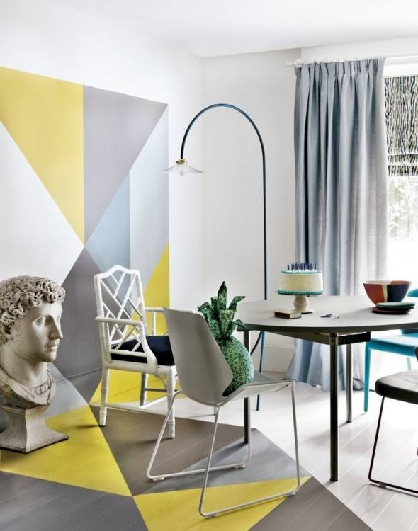 a bright dining room done with geometric color blocj, grey and white chairs, a modern table and a catchy floor lamp