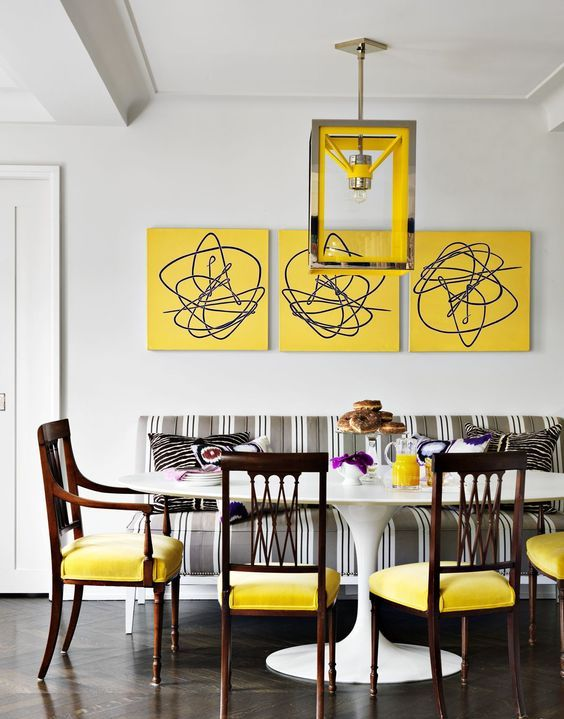 a bright dining room with a vintage feel - a bold yellow gallery wall, a grey striped sofa, yellow chairs and a catchy pendant lamp