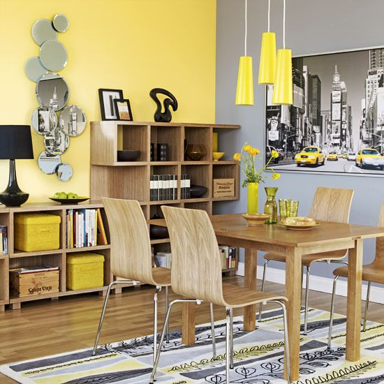 a bright grey and yellow dining room with a grey and a yellow accent wall, an open storage unit, a stylish dining set and lemon yellow pendant lamps