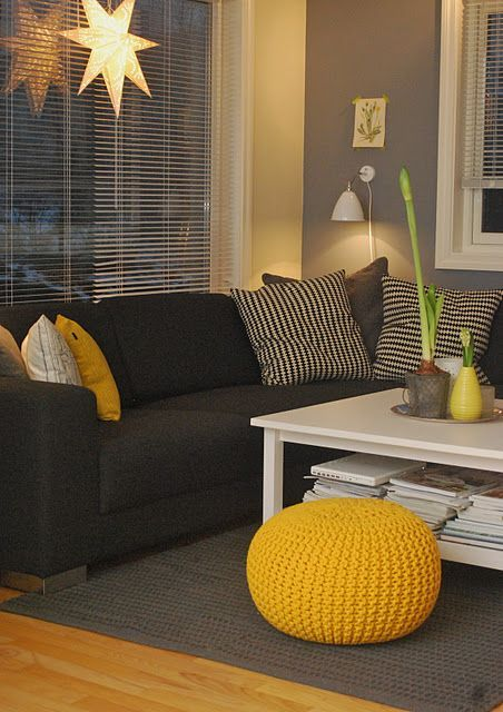 a bright living room with a black sectional, grey walls and a grey rug, sunny yellow accessories and lamps and lights